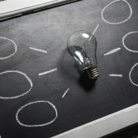 Eine Glühbirne auf einer Tafel steht symbolisch für neue Ideen - passend zur Wirksamkeit von Coaching