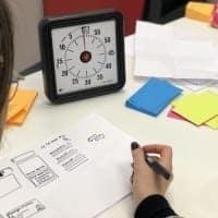 Tisch mit Stoppuhr und Schreibunterlagen stellt einen der Coachee-Plätze von Competence on Top dar.