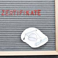 Zertifikat und Absolventenhut auf Letterboard - anschaulich für das Coaching-Zertifikat