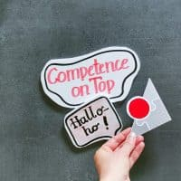 Hand mit Halloho und Logo von Competence on Top, da die Präsenzkurse wieder starten.